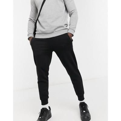 ゲス メンズ カジュアルパンツ ボトムス Guess skinny cuffed sweatpants in black with small logo