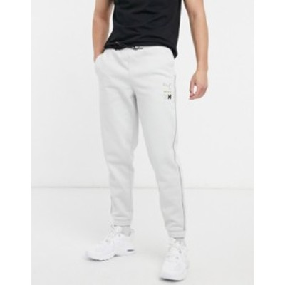 プーマ メンズ カジュアルパンツ ボトムス Puma x Helly Hansen logo taped sweatpants in gray Glacier gray